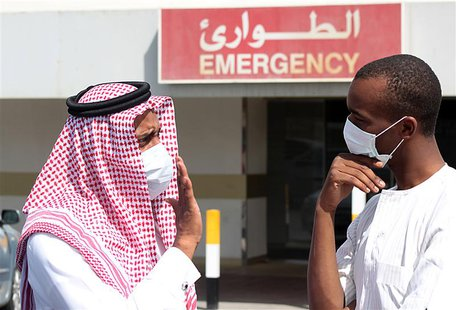 Men wearing surgical masks as a precautionary measure against the novel coronavirus, speak at a hospital in Khobar city in Dammam May 23, 20