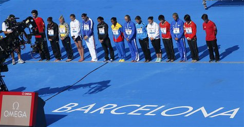 Competitors take part in a minute's silence for the victims of the train crash near Santiago de Compostela, before the women's 10m platform