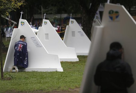 A man with the Australian flag confesses at the confessional booths set up at Quinta da Boa Vista park at the World Youth Day in Rio de Jane
