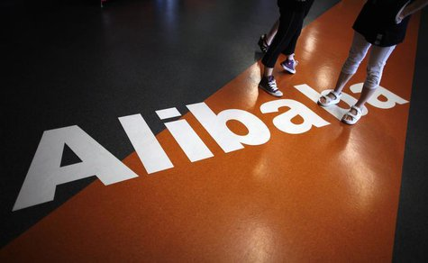 Employees stand on a logo of Alibaba (China) Technology Co. Ltd during a media tour organised by government officials at its headquarters on