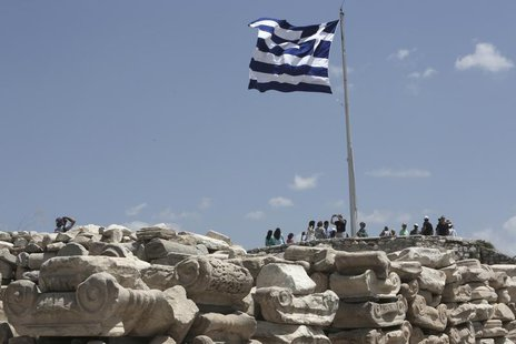 A Greek flug flutters at the top of the Acroplis hill in Athens July 2, 2013. REUTERS/John Kolesidis