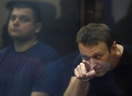 Russian protest leader Alexei Navalny (R) and his co-defendant Pyotr Ofitserov sit in a glass-walled cage during a court session in Kirov, J