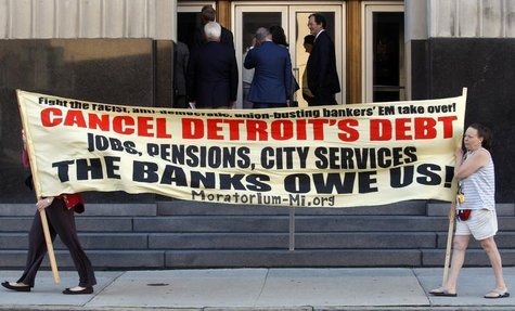 Protesters carry a banner calling for Detroit's debt to be cancelled as people enter the federal courthouse for day one of Detroit's municip