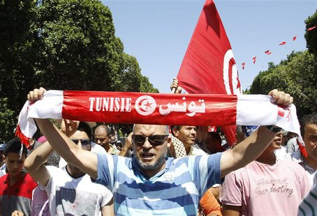 A supporter of the Islamist Ennahda movement holds up a scarf as he chants slogans during a demonstration in Tunis July 26, 2013. REUTERS/Zo