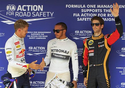 Mercedes Formula One driver Lewis Hamilton (C) of Britain shakes hands with Red Bull Formula One driver Sebastian Vettel (L) of Germany as L
