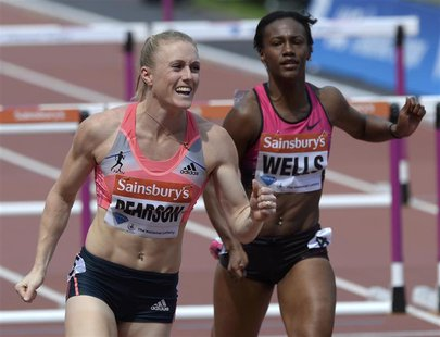 Sally Pearson (L) of Australia reacts next to third-placed Kellie Wells of the United States after winning the women's 100m hurdles at the L
