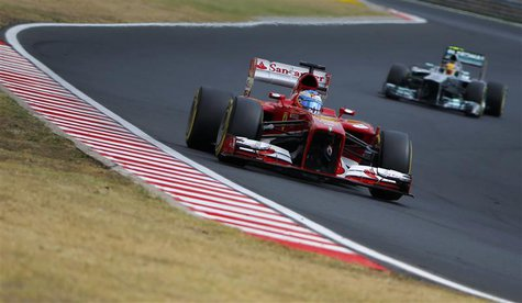 Ferrari Formula One driver Fernando Alonso of Spain drives ahead of Mercedes Formula One driver Lewis Hamilton (R) of Britain during the qua
