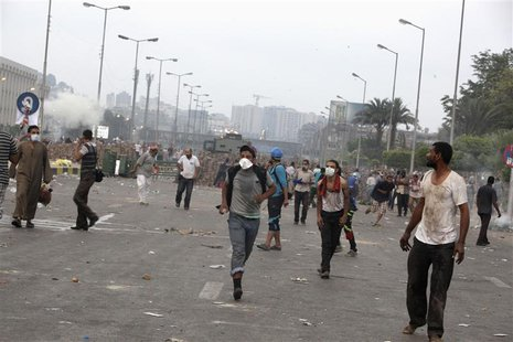 Supporters of deposed Egyptian President Mohamed Mursi run from tear gas thrown at pro-Mursi protesters by police during clashes in Nasr cit