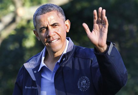 U.S. President Barack Obama waves as he walks on the South Lawn of the White House upon his return to Washington from Camp David, July 26, 2
