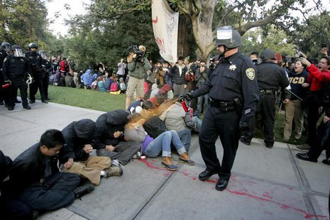 "A University of California Davis police officer pepper-sprays students during their sit-in at an ""Occupy UCD"" demonstration in Davis, Califo"