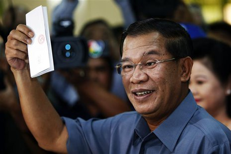 Cambodia's Prime Minister Hun Sen shows his ballot before casting it in the general elections at a polling station in Kandal province July 2