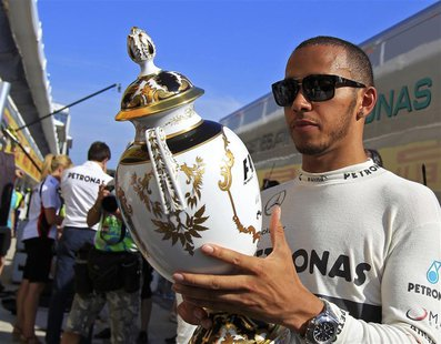 Mercedes Formula One driver Lewis Hamilton of Britain looks at his trophy after winning the Hungarian F1 Grand Prix at the Hungaroring circu