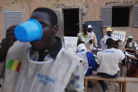 A poll worker breaks his Ramadan fast with water as other workers count ballots after the end of voting in Mali's presidential elections in