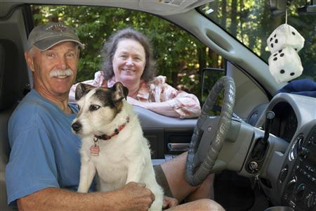 Kent Holder, a volunteer with Fox Island Citizens' Patrol, poses for a portrait with his wife, Ann, who is also a volunteer, and dog, Badger, for Reuters on Fox Island, Washington July 27, 2013. Credit: Reuters/David Ryder