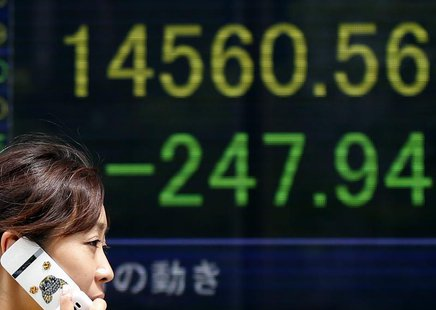 A woman walks past a stock quotation board displaying Japan's Nikkei average outside a brokerage in Tokyo July 19, 2013. REUTERS/Toru Hanai