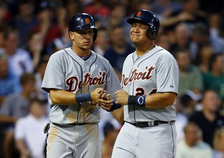 Detroit Tigers third baseman Miguel Cabrera (R) grimaces as he celebrates after scoring in the top of the fifth inning with teammate Hernan