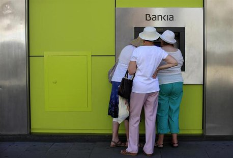 People use an ATM machine at a branch of Spain's nationalized lender Bankia in the Andalusian capital of Seville, southern Spain, June 24, 2