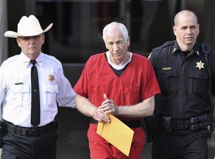 Jerry Sandusky (C) leaves the Centre County Courthouse after his sentencing in his child sex abuse case in Bellefonte, Pennsylvania October