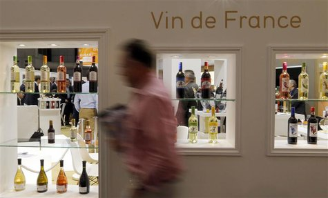 A visitor walks past wine bottles displayed at Vinexpo, the world's biggest wine fair, in Bordeaux, southwestern France, June 18, 2013. REUT