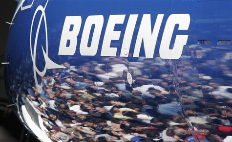 Invited guests for the world premiere of the Boeing 787 Dreamliner are reflected in the fuselage of the aircraft at the 787 assembly plant i