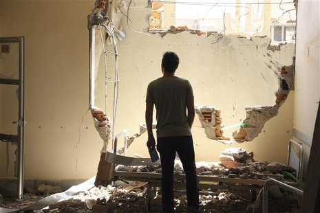 A man inspects damage at a hospital in Deir al-Zor July 28, 2013. REUTERS/Karam Jamal