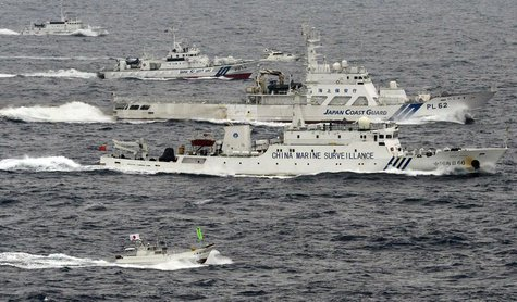 An aerial photo shows a Chinese marine surveillance ship Haijian No. 66 (C) cruising next to Japan Coast Guard patrol ships in the East Chin
