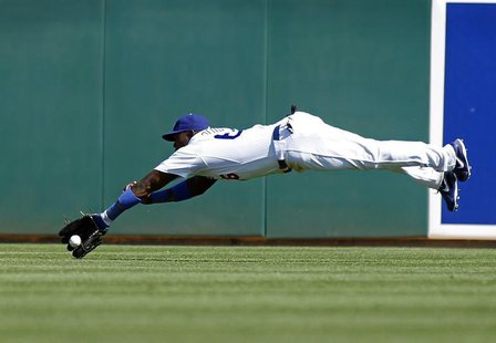 Los Angeles Dodgers center fielder Yasiel Puig attempts to make a diving catch of a fly ball off the bat of Cincinnati Reds' Brandon Phillip