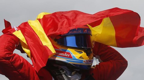 Ferrari Formula One driver Fernando Alonso of Spain holds up his national flag as he celebrates winning the Spanish F1 Grand Prix at the Cir