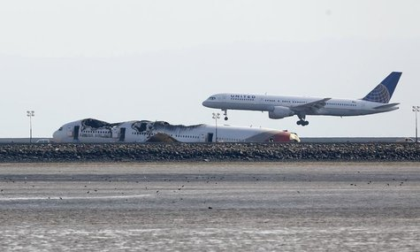 An aircraft lands behind the wreckage of the Asiana Airlines plane at San Francisco International Airport in San Francisco, California, July