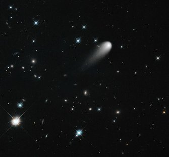 The sun-approaching Comet ISON floats against a seemingly infinite backdrop of numerous galaxies and a handful of foreground stars in this A