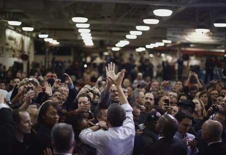U.S. President Barack Obama high-fives an employee of the Daimler Detroit Diesel plant following remarks and a tour in Redford, Michigan, De