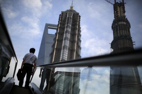 A man rides an escalator near Shanghai Tower (R, under construction), Jin Mao Tower (C) and the Shanghai World Financial Center (L) at the P