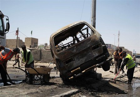 Street cleaners remove debris on the road at the site of a car bomb attack in Basra, 420 km (260 miles) southeast of Baghdad, July 29, 2013.