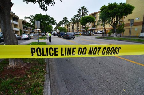 Police tape blocks the street to an apartment building after a shooting incident which began Friday evening left seven people dead in Hialea