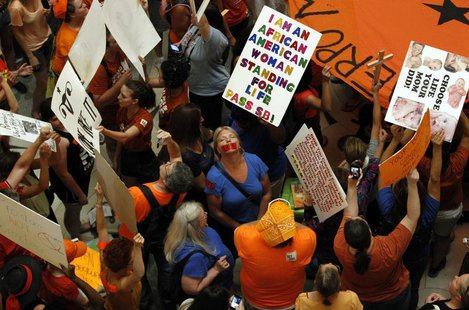 Abortion rights (in orange) and anti-abortion advocates (in blue) rally in the rotunda of the State Capitol, as the state Senate meets to co