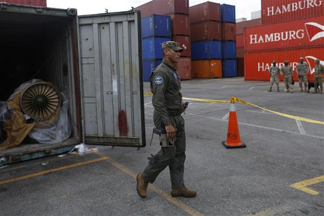 A police officer walks next to a container holding a MiG-21 fighter jet engine from the seized North Korean-flagged ship Chong Chon Gang, at
