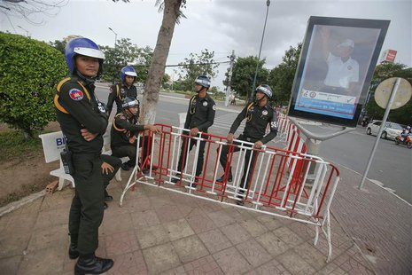 Military policemen stand in front of a poster of Cambodia's long-ruling Prime Minister Hun Sen in central Phnom Penh July 30, 2013. REUTERS/