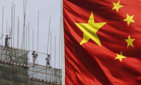 Labourers working at a construction site are pictured behind a Chinese flag in Beijing April 24, 2013. REUTERS/Kim Kyung-Hoon