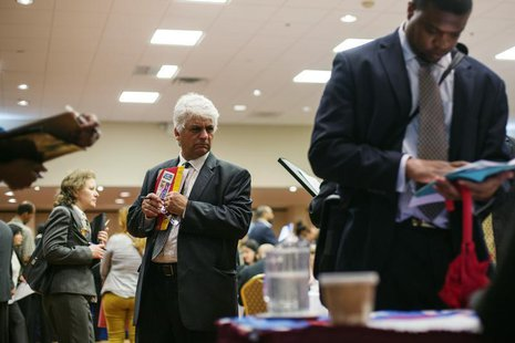 A man walks past job seekers as they fill out job applications for recruiters during a job fair in New York, June 11, 2013. REUTERS/Lucas Ja