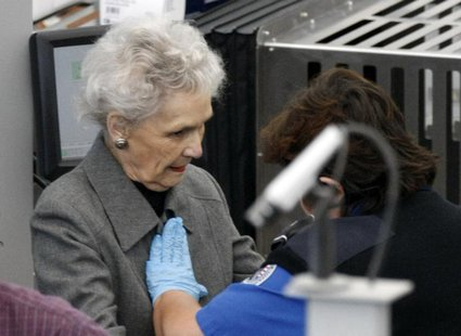 A Transportation Security Administration (TSA) worker (R) rubs her hands across a elderly female traveler's chest during a patdown search at