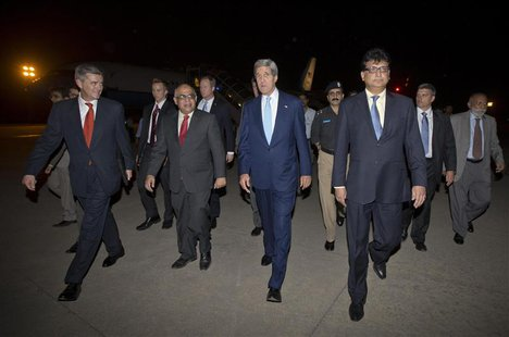 U.S. Secretary of State John Kerry (C) walks with U.S. Ambassador to Pakistan Richard Olson (L) and unidentified Pakistani officials upon hi
