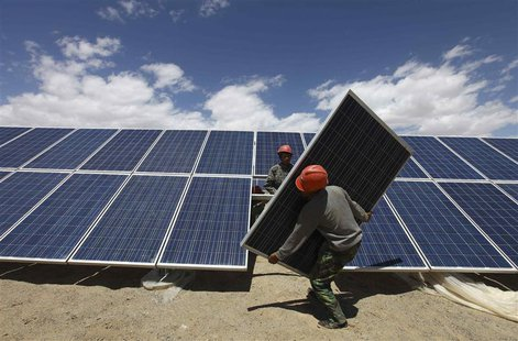 Workers install a solar panel in Jiuquan, Gansu province, in this July 14, 2013 file photo. REUTERS/Stringer/Files
