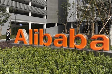 A security guard walks past a logo of Alibaba (China) Technology Co. Ltd at its headquarters on the outskirts of Hangzhou, Zhejiang province