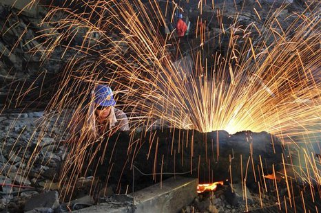 A labourer cuts scrap steel at a factory of Dongbei Special Steel Group Co., Ltd., in Dalian, Liaoning province July 24, 2013. REUTERS/China