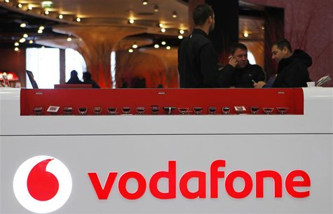 The Vodafone logo is seen at the counter of the shop as customers look at mobile phones in Prague February 7, 2012. British telecommunicatio