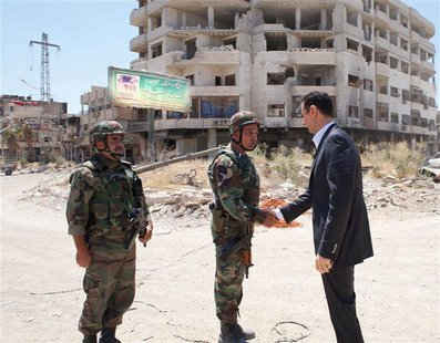 Syria's President Bashar al-Assad (R) shakes hands with a military personnel during his visit to a military site at Darya area, on the occas