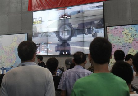 "Visitors look at a screen, displaying the video game ""Glorious Mission Online"", under a Chinese national flag during the China Digital Enter"