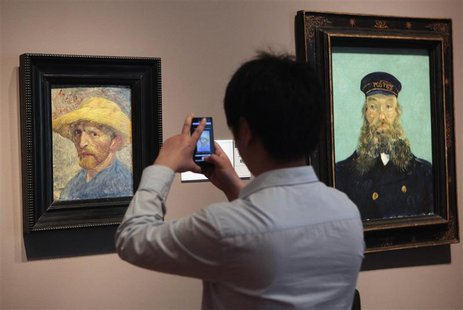 A visitor uses his cell phone to take a picture of the 'Self Portrait' painting by painter Vincent van Gogh at the Detroit Institute of Arts