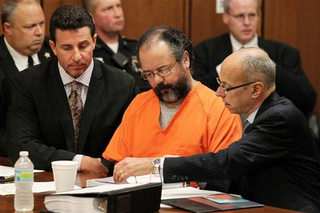 Ariel Castro (C), 53, sits as his attorneys Craig Weintraub (L) and Jaye Schlachet (R) review documents during Castro's sentencing on Kidnap