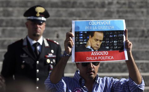A man holds up a picture of former Italian Prime Minister Silvio Berlusconi as he protests in front of Italy's supreme court building in Rom